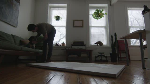 WS SLO MO. Young artist pets dog on couch with blank canvas on apartment floor.