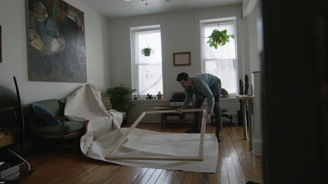 vídeos de stock, filmes e b-roll de ws slo mo. young artist places wooden frame on unfurled canvas on apartment floor. - cômodo de casa