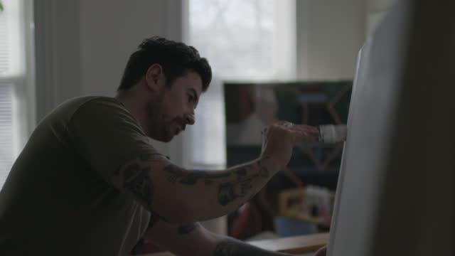 vidéos et rushes de ms slo mo. young artist primes blank canvas with paintbrush. - toile à peindre