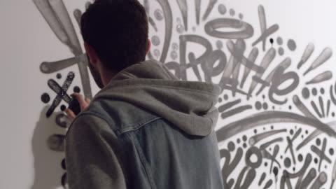 vídeos y material grabado en eventos de stock de slo mo. young artist spraypaints black x and walks away from graffiti mural in white studio. - arte