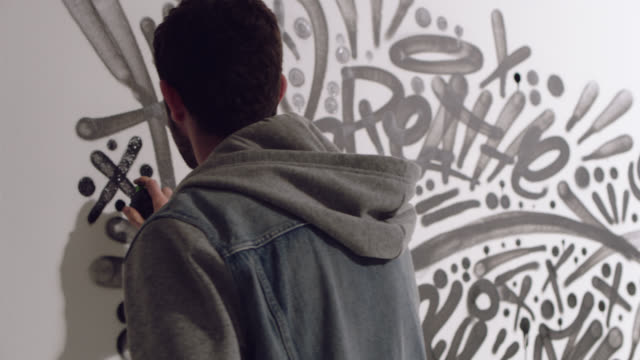 SLO MO. Young artist spraypaints black X and walks away from graffiti mural in white studio.
