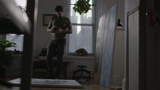WS SLO MO. Young artist takes smartphone photo of painting and texts it to friends.