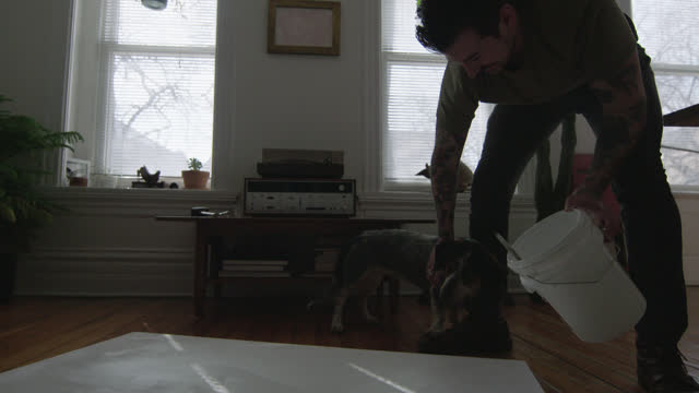 WS SLO MO. Young artist with paint bucket pets dog in apartment workspace.