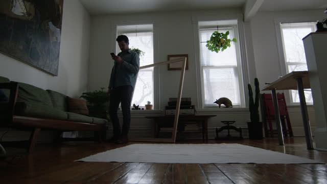 WS SLO MO. Young artist with smartphone stands over spread canvas on apartment floor.