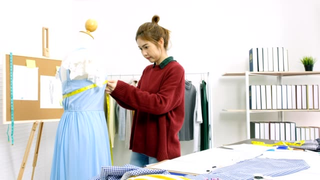 Young asia fashion designer measuring dress on mannequin at her home office, fashion industry, working at home, small business owner