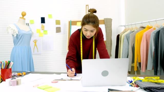 若いアジア fasian デザイナー女性ラップトップ コンピューターを使用して、ホーム オフィスの背景、彼女の机にノートブック紙の上にスケッチ ファッション産業、中小企業オーナーのコン� - トルソー点の映像素材/bロール