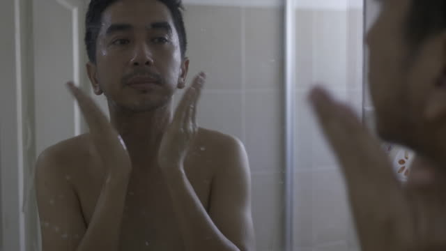 young asia man applying cream on face looking in mirror - mirror object stock videos & royalty-free footage