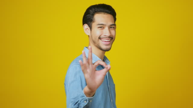 young asia man smiling and showing his okay sign, happy asia male looking at camera while showing ok gesture standing over yellow background in studio, head shot, 4k resolution - ok sign stock videos & royalty-free footage