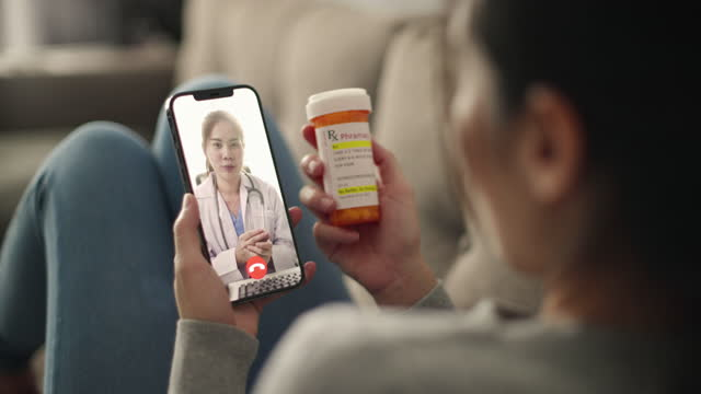 young asia patient talking with her doctor on smart phone video call conference medical app in telehealth telemedicine online service hospital quarantine social distance at home concept. - video stock videos & royalty-free footage