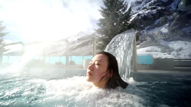 Junge asiatische Frau Genießen Sie die heißen Quellen in der Schweiz