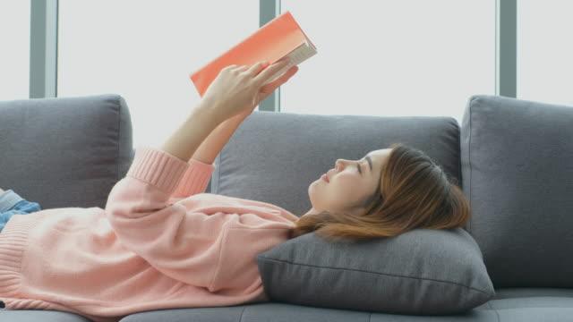 unga asien kvinna läsebok med lycka medan du sitter på soffan med stadsutsikt, människor livsstil, utbildning - litteratur bildbanksvideor och videomaterial från bakom kulisserna