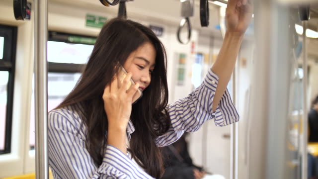 giovane donna asiatica che usa uno smartphone in metropolitana - east asian ethnicity video stock e b–roll