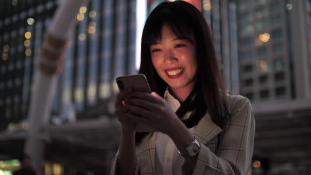 young asia woman using tablet with beautiful bokeh in city view - southeast asia stock videos & royalty-free footage