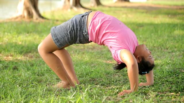 若いアジア脂肪の女の子公園でヨガ - 弓のポーズ点の映像素材/bロール