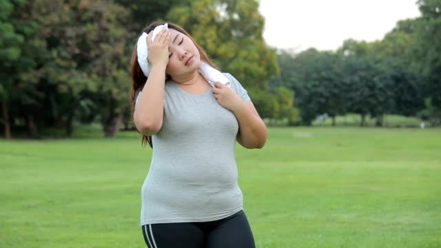 公園で若いアジアの太った女性が疲れています。 - overweight点の映像素材/bロール