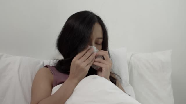 young asian adult lying on bed suffering with cold, holding paper tissue and sneezing feeling bad. - tissue paper stock videos & royalty-free footage