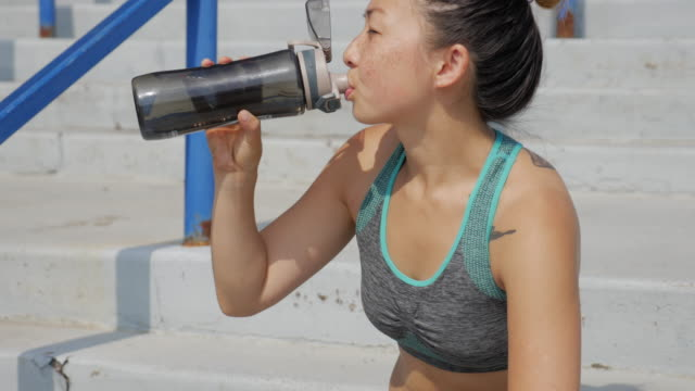 young asian athlete woman drinks water after running on the stairs - bottiglia d'acqua video stock e b–roll