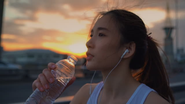 young asian athlete woman drinks water after running,close-up - drinking stock videos & royalty-free footage