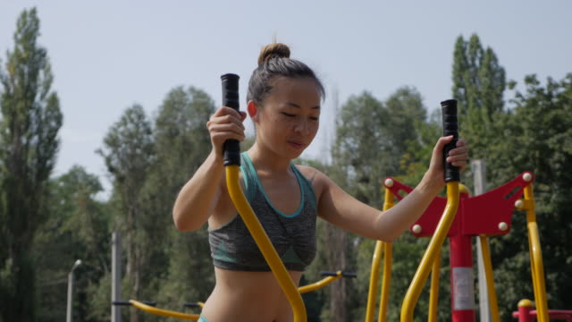 young asian athlete woman engaged in the simulator  in the park - kharkov stock videos & royalty-free footage