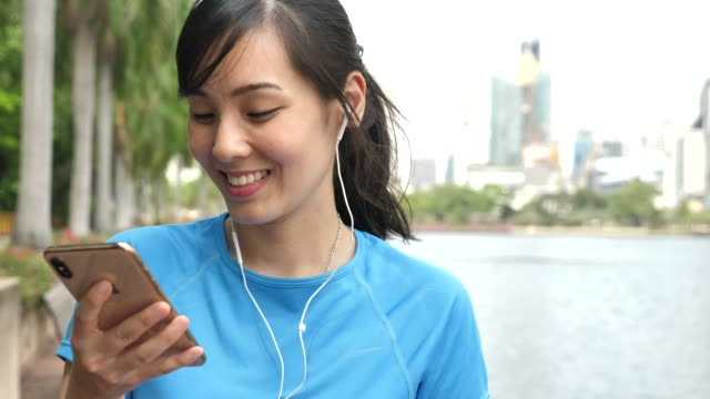 Young Asian athletic woman listening to music on smart phone
