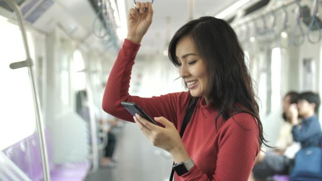vidéos et rushes de la jeune belle femme asiatique emploie le téléphone intelligent dans les transports publics - métro transport ferroviaire