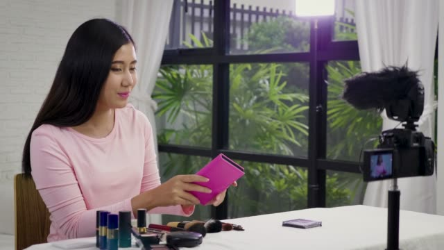 Young Asian beauty blogger present cosmetic product and recording her make up tutorial video to social network by internet at home