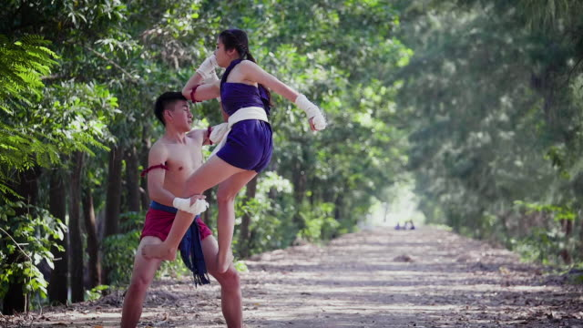 vídeos de stock e filmes b-roll de young asian boxer couple or muay thai fighter training or the fight at outdoors, thai boxing and martial arts concept - elbow