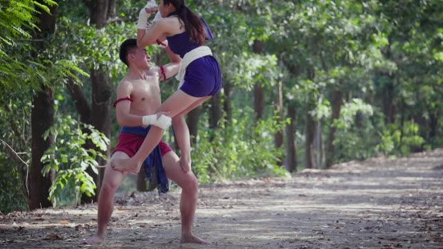vídeos y material grabado en eventos de stock de pareja joven boxeador asiático, luchador de muay thai entrenamiento o la lucha en al aire libre, el boxeo tailandés y el concepto de artes marciales - codo
