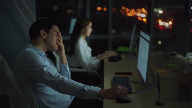 若いアジアのビジネスマンは、仕事の残業後に疲れを感じています - 心配する点の映像素材/bロール