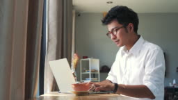 Young Asian business man working with laptop computer while sitting in coffee shop cafe