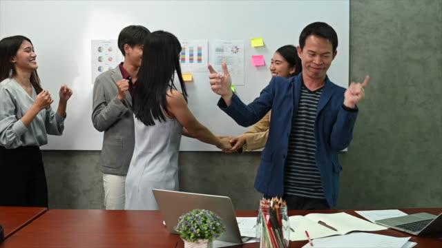 vidéos et rushes de jeunes gens asiatiques de bureau d'affaires avec la danse occasionnelle intelligente de tissu dans le bureau moderne, concept de travail d'humeur heureuse - collègue