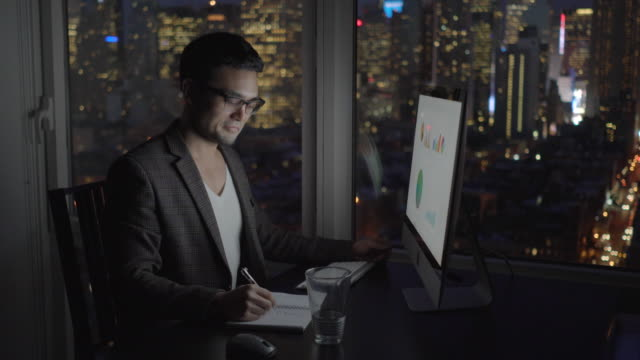 Young asian business professional working on computer in modern city office