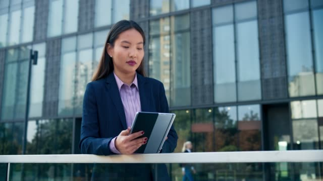 ds young asian business woman scrolling on her tablet in front of a modern business building - office block exterior stock videos & royalty-free footage