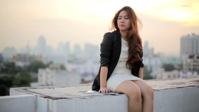 Junge asiatische Geschäftsfrau betont Arbeitsplätze auf Sonnenuntergang