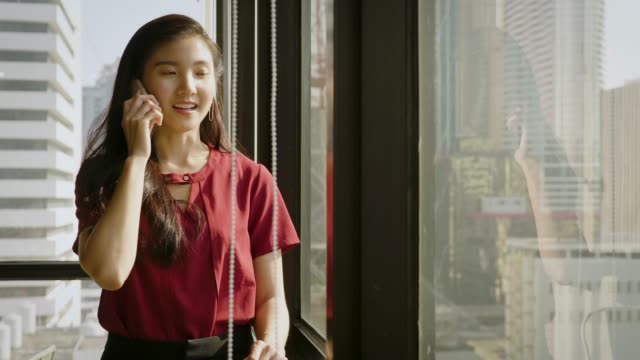 Young Asian business woman using smart phone next to window at office