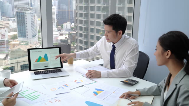 Young Asian businessman discussing sales with team