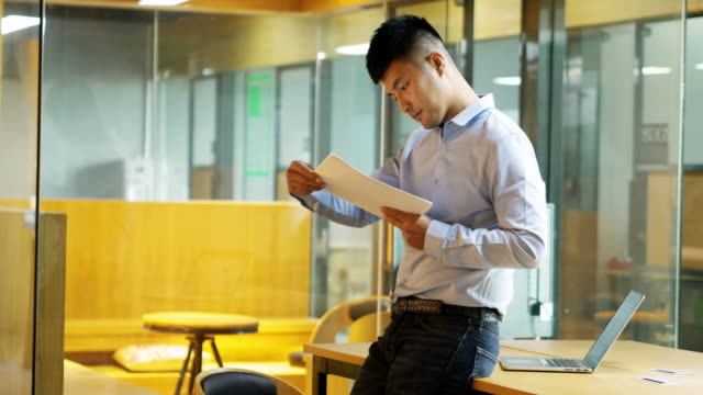young asian businessman read business report in office - business report stock videos & royalty-free footage