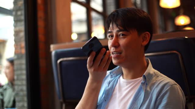 vídeos de stock, filmes e b-roll de homem de negócios asiático novo usando o telefone de pilha que emite o correio de voz - voz