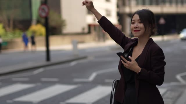 young asian businesswoman in city hailing for her ride with mobile phone on her hand - three quarter length stock videos & royalty-free footage