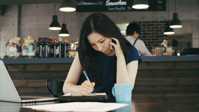 Young Asian Businesswoman Taking Order by Phone and Laptop