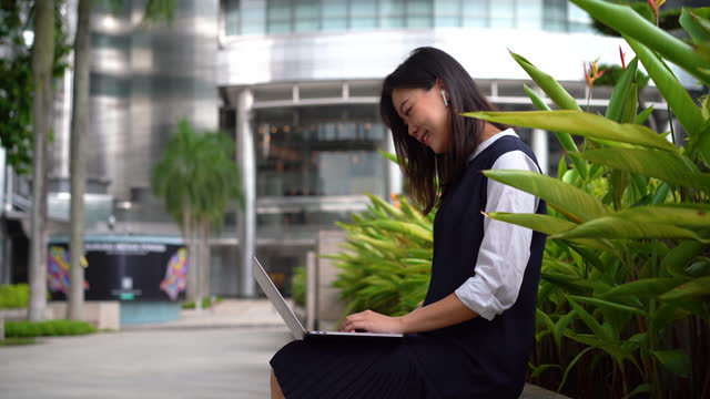 young asian businesswoman using laptop at an outdoor park in the city - petronas twin towers stock videos & royalty-free footage