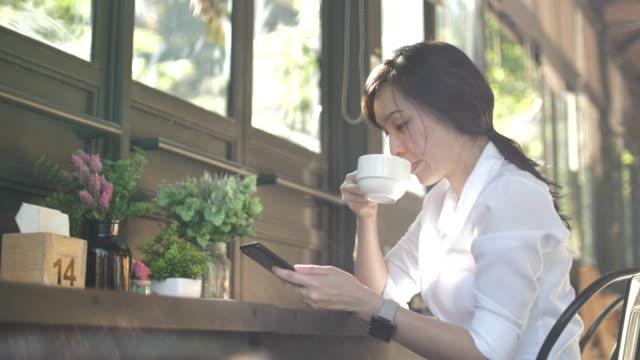 vídeos y material grabado en eventos de stock de jóvenes asiáticos empresaria usando smart phone en cafe (cámara lenta) - chino oriental