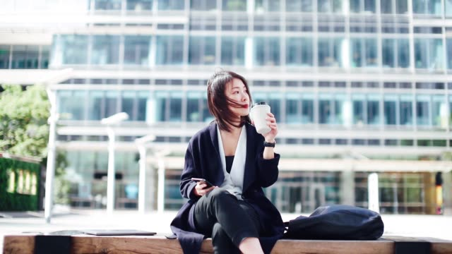 young asian businesswoman using smart phone while drinking coffee in financial district - short hair stock videos & royalty-free footage