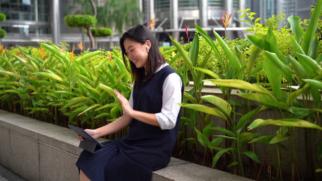 young asian businesswoman video call using a digital tablet at an outdoor park in the city - petronas twin towers stock videos & royalty-free footage