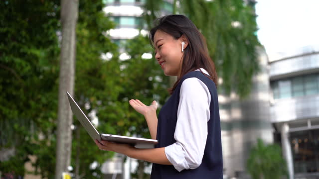 young asian businesswoman video call using a laptop at an outdoor park in the city - petronas twin towers stock videos & royalty-free footage