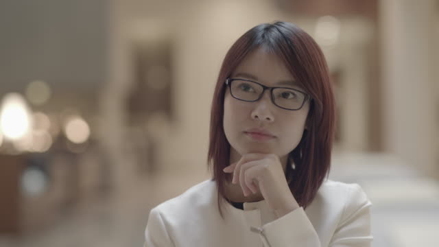 young asian businesswoman wearing glasses and waiting in lobby. holding hand to the chin. - mittellanges haar stock-videos und b-roll-filmmaterial