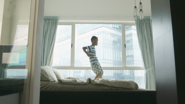 young asian children having fun jumping on a bed - malay family stock videos and b-roll footage
