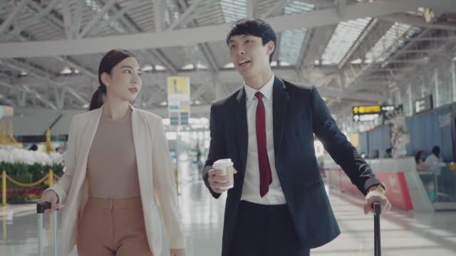 junge asiatische paar asiatisch am flughafen. - flugpassagier stock-videos und b-roll-filmmaterial
