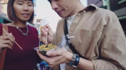 Young asian couple buy fired insects in a street food marketplace in Bangkok, at Khao San Road