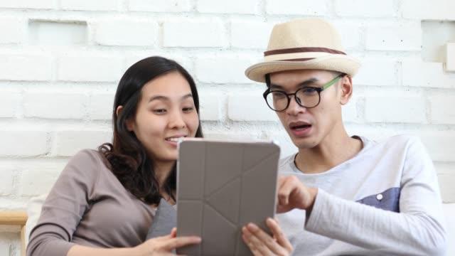 stockvideo's en b-roll-footage met jonge aziatische paar kopen goederen vormen internet - videoportret
